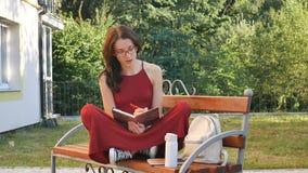 Młoda brunetka w eyeglasses siedzi na brench outdoors i pisze coś żeński uczeń w czerwieni sukni uczenie zbiory wideo