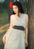 Młoda brunetka w polki kropki smokingowy pozuje opierać przeciw drzewu obraz stock