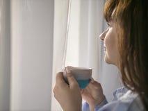Młoda brunetka z filiżanka kawy spojrzeniami za okno, w górę zdjęcie royalty free
