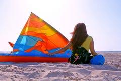 Młoda brunetki dziewczyna siedzi odpoczywać na seashore z naleśnikowym włosy w, hełm i obraz royalty free