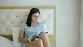 Młoda brunetki dziewczyna Używa pastylka peceta Kłama Na łóżku Przy rankiem zbiory