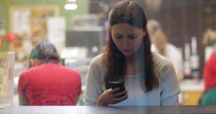 Młoda brunetki dziewczyna używa smartphone w kawiarni zbiory wideo