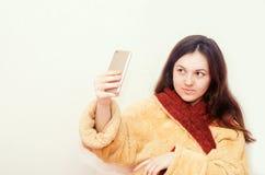 Młoda brunetki dziewczyna w bathrobe robi selfie na białym odosobnionym tle fotografia royalty free