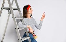 Młoda brunetki dziewczyna z drabiną i muśnięciem - wskazuje przestrzeń dla twój reklamy zdjęcia royalty free