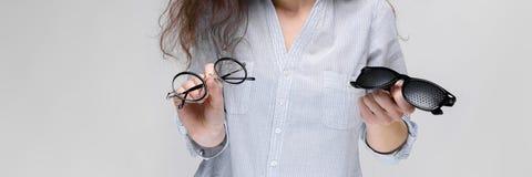 Młoda brunetki dziewczyna z szkłami Dziewczyna trzyma dwa pary szkła fotografia royalty free