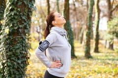 Młoda brunetki kobieta łapie jej oddech po biegać w parku obrazy royalty free