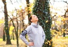 Młoda brunetki kobieta łapie jej oddech po biegać w parku obrazy stock