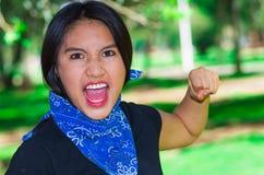 Młoda brunetki kobieta jest ubranym błękitne bandany wokoło szyi, oddziała wzajemnie outdoors dla kamery, aktywisty protestacyjny Zdjęcia Royalty Free