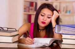 Młoda brunetki kobieta jest ubranym menchii odgórnego obsiadanie biurkiem z stertą książki umieszczać na nim, odpoczynkowa głowa  Zdjęcia Stock