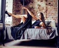 Młoda brunetki kobieta kłaść na łóżkowy ono uśmiecha się w loft zdjęcia stock