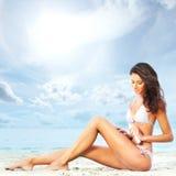 Młoda brunetki kobieta kłaść na plażowym tle Zdjęcie Stock