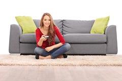 Młoda brunetki kobieta ogląda TV Obraz Stock