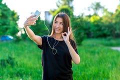 Młoda brunetki kobieta ono uśmiecha się szczęśliwie w lecie w parku Komunikuje w ogólnospołecznych sieciach Ręka gesty ok, I ` m  Obraz Royalty Free
