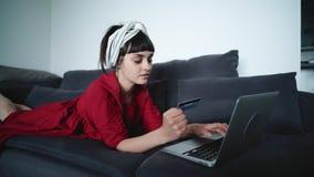 Młoda brunetki kobieta płaci dla rzeczy online z kartą zbiory wideo