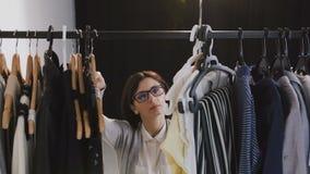 Młoda brunetki kobieta patrzeje przez poręcza odzież na wieszakach w szkłach Młody caucasian kobiety wybierać odziewa dalej zdjęcie wideo