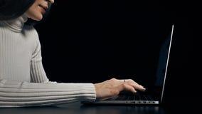 Młoda brunetki kobieta pisać na maszynie na jej laptopie przeciw czarnemu tłu 4K wideo zdjęcie wideo