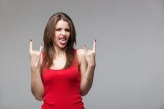 Młoda brunetki kobieta pokazuje rock and roll ręki gest pozuje w studiu Zdjęcie Stock