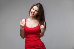 Młoda brunetki kobieta pokazuje rock and roll ręki gest pozuje w studiu Zdjęcia Stock