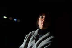 Młoda brunetki kobieta ssa jej policzki nad czarnym tłem fotografia stock