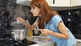 Młoda brunetki kobieta stoi bezczynnie kuchenkę w kuchni na czarnym tle, wącha ładnych aromaty od jej posiłku wewnątrz zbiory wideo