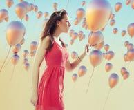 Młoda brunetki kobieta wśród balonów Obraz Stock