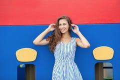 Młoda brunetki kobieta w świetle paskował białą błękit suknię ma zabawę przy boiskiem plenerowym Obraz Royalty Free