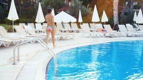 Młoda brunetki kobieta w bikini i okularach przeciwsłonecznych dostaje out pływackiego basenu na Pogodnym letnim dniu zbiory wideo