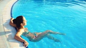 Młoda brunetki kobieta w bikini w basenie na Pogodnym letnim dniu zbiory