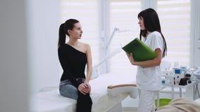 Młoda brunetki kobieta w eleganckiej odzieży siedzi w cosmetologist's gabinecie beautician egzamininuje jej twarz, one zdjęcie wideo