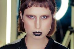 Młoda brunetki kobieta wzrasta spojrzenie w kamerze z czarnymi wargami głębokość pola płytki zdjęcia stock