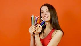Młoda brunetki kobieta z Kolorowymi ołówkami Pozuje na Pomarańczowym tle sztuka projekta pojęcie zbiory wideo