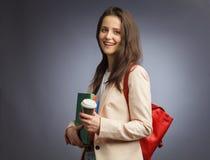 Młoda brunetki kobieta z kopii książką na pracownianym tle Zdjęcie Stock