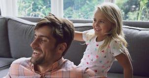 Młoda córka czesze ona w domu ojcowie włosiani na kanapie 4k zdjęcie wideo