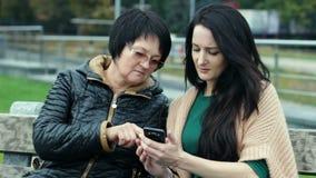 Młoda córka jest jej matce uczący dlaczego używać smartphone Dwa brunetki różni wieki siedzą na ławce zbiory