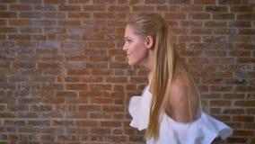 Młoda caucasian blondynka w białej bluzki śmiesznym tanu, ściana z cegieł w tle