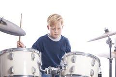 Młoda caucasian chłopiec przy bębenu zestawem w studiu bawić się muzykę zdjęcia royalty free