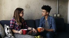 Młoda caucasian dziewczyna i przystojny oliwkowy facet oba jest ubranym miastowi stroje, siedzi na leżance z filiżankami herbata, zbiory wideo