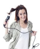 Młoda caucasian dziewczyna używa fryzowania żelazo Fotografia Stock