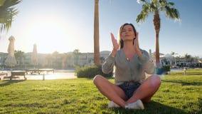 Młoda caucasian kobieta relaksuje ćwiczyć joga na zielonej trawy jasnego błękitnym basenie, gyan mudra i lotosowej pozycji blisko zbiory