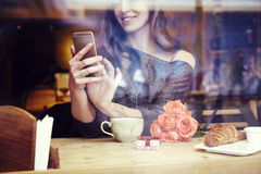 Młoda caucasian kobieta z długie włosy siedzącym pobliskim okno w kawiarni Obrazy Royalty Free
