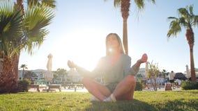 Młoda caucasian kobieta zmniejsza stres relaksuje ćwiczyć joga na zielonej trawie, gyan mudra i lotosowej pozycji, Wschód słońca zdjęcie wideo