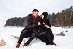 Młoda caucasian para w miłości siedzi na kamieniu z psem na zimy plaży, obejmowanie, cieszy się romantycznego moment, czuciowa in obrazy royalty free
