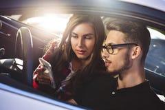Młoda caucasian para w samochodzie ma zabawę na wycieczce samochodowej i używa smartphone zdjęcie stock
