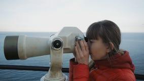 Młoda caucasian z włosami kobieta patrzeje dennego wybrzeże w teleskop od wysokiej podwyższonej obserwaci zdjęcie wideo