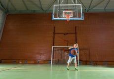 Młoda chłopiec ćwiczy jego koszykówkę Fotografia Royalty Free