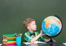 Młoda chłopiec bada kulę ziemską Obrazy Royalty Free