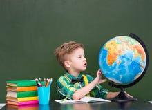 Młoda chłopiec bada kulę ziemską Fotografia Stock