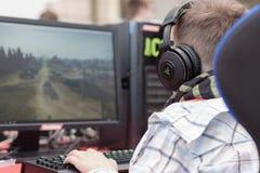 Młoda chłopiec bawić się grę na osobistym komputerze przy Animefest zdjęcia royalty free