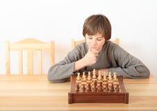 Młoda chłopiec bawić się szachy Obrazy Stock
