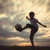 Młoda chłopiec bawić się w polu z piłki nożnej piłką Zdjęcia Royalty Free